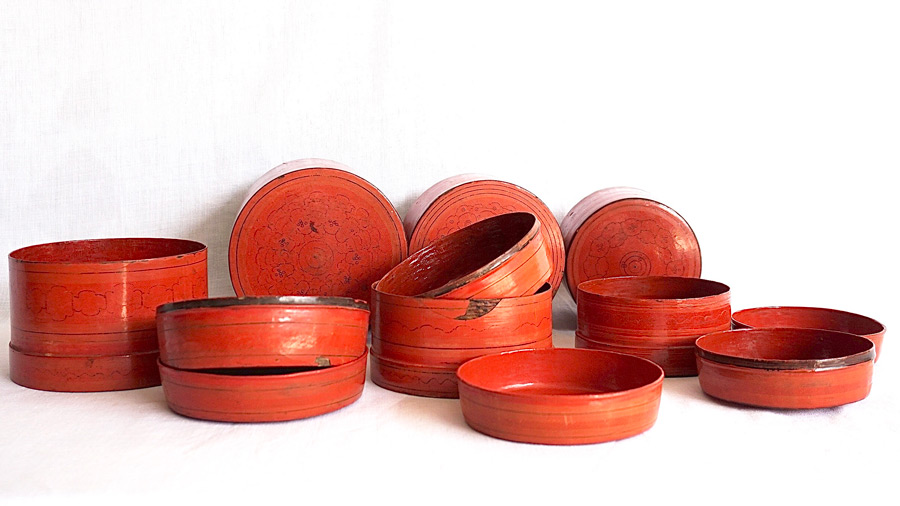 a collection of red Burmese lacquerware